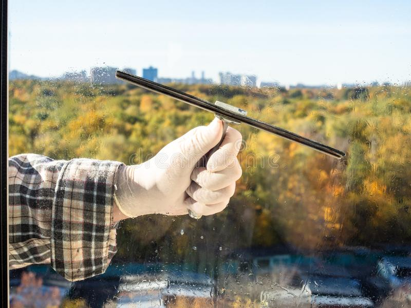 cleaning a home window glass by squeegee royalty free stock images