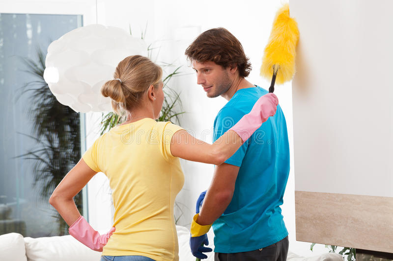 Cleaning house. Young people in love cleaning house stock photography