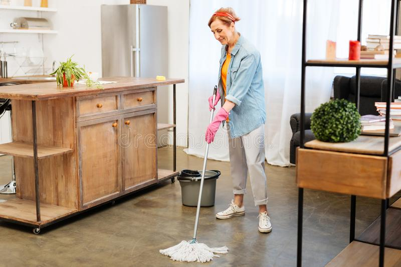 Concentrated positive woman in domestic outfit washing floor with mop. Cleaning house. Concentrated positive woman in domestic outfit washing floor with mop stock images