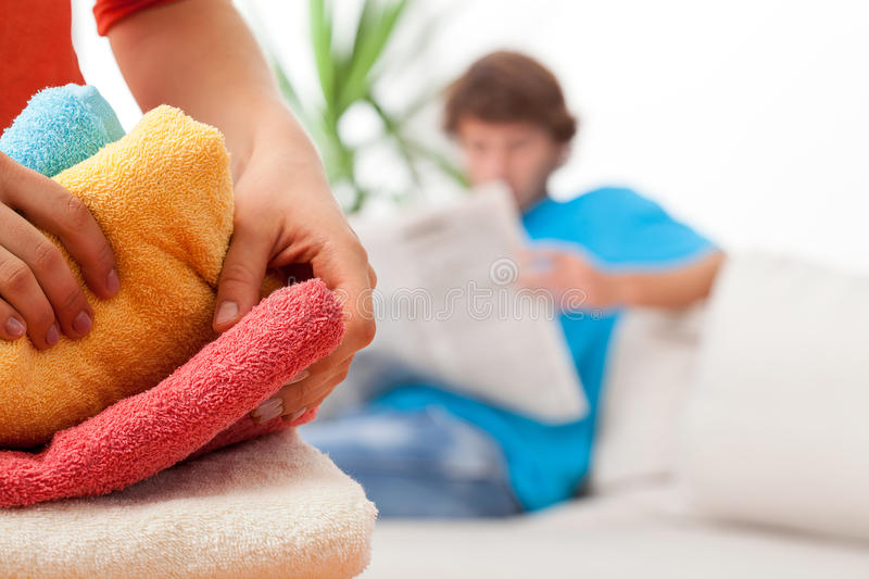 Cleaning house. Woman arranging towels during cleaning in house royalty free stock photography