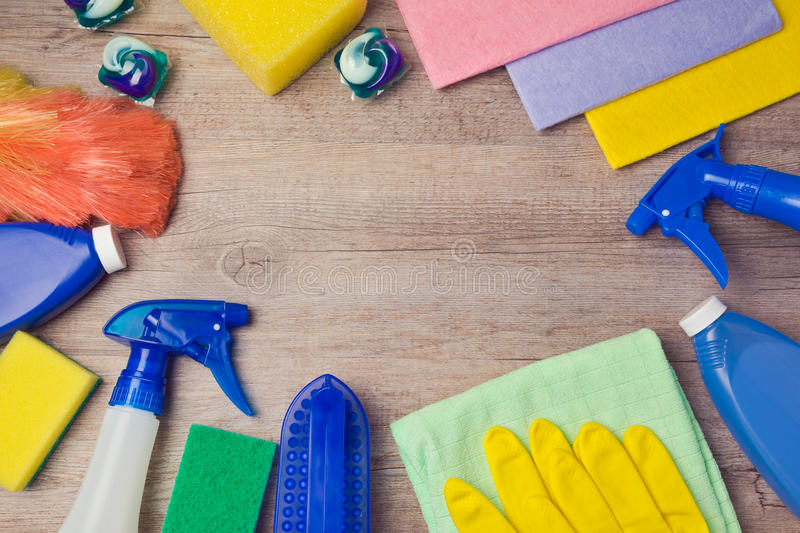 Cleaning and household concept with supplies on wooden background. View from above. Cleaning and household concept with supplies on wooden background stock photos
