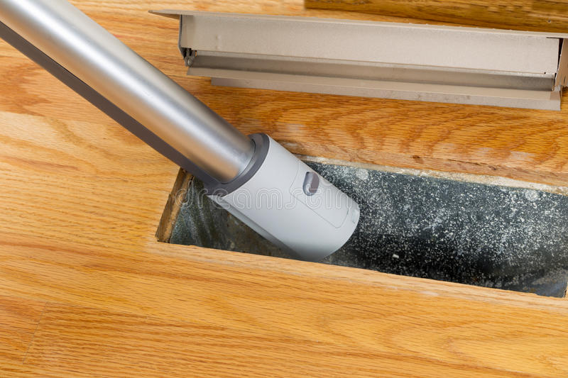 Cleaning inside heating floor vent with Vacuum Cleaner. Horizontal photo of vacuum cleaning inside heater floor vent with Red Oak Floors in background stock photos
