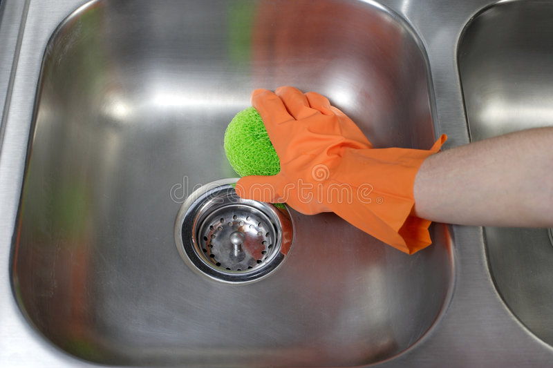 Cleaning Kitchen Sink. A person cleaning the kitchen sink with a glove stock image