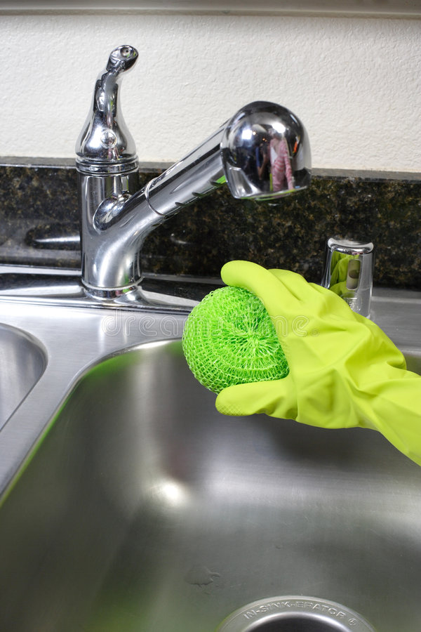Cleaning Kitchen Sink. A person cleaning the kitchen sink with a glove stock photo