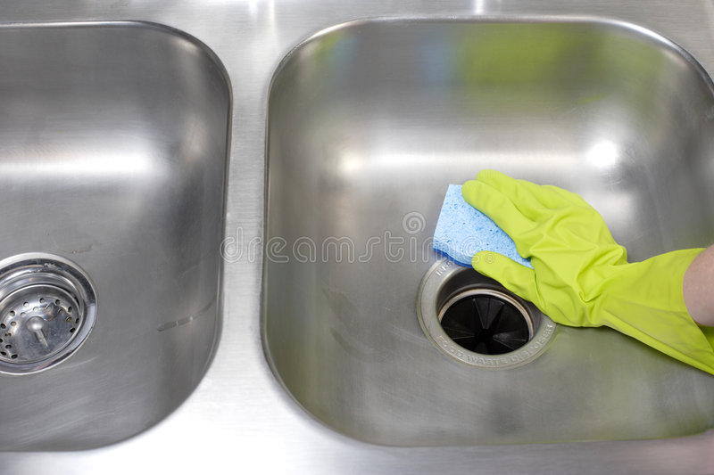 Cleaning Kitchen Sink. A person cleaning the kitchen sink with a glove royalty free stock photography