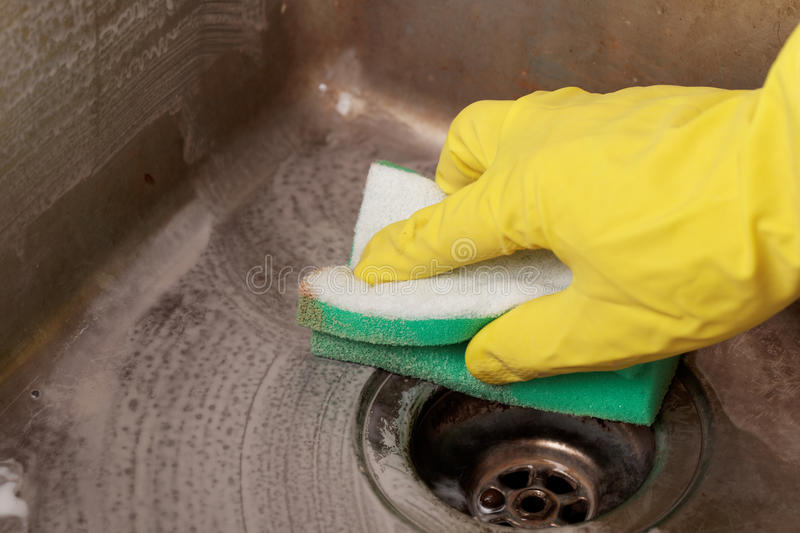 Cleaning kitchen sink. Cleaning a kitchen sink using cleaning sponge and cleaner royalty free stock image