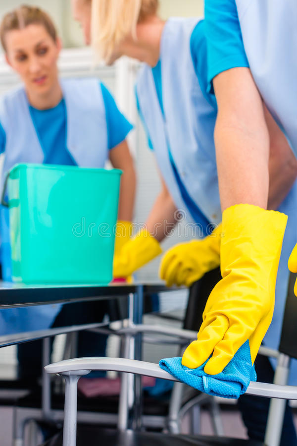 Cleaning ladies working as team in office stock images