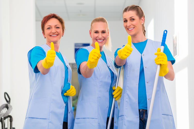 Cleaning ladies working in team. Showing the thumbs up sign royalty free stock image