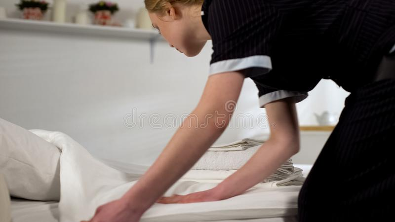 Cleaning lady making bed, preparing hotel room for new guests arrival, service. Stock photo stock images