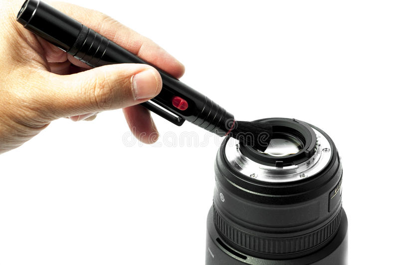 Cleaning lens. Hand holding a lens cleaner cleaning a lens stock photography