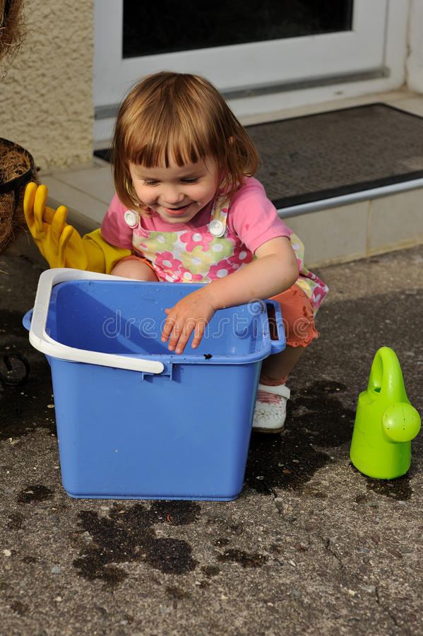Cleaning. A little girl crouching next to a blue bucket stock photos