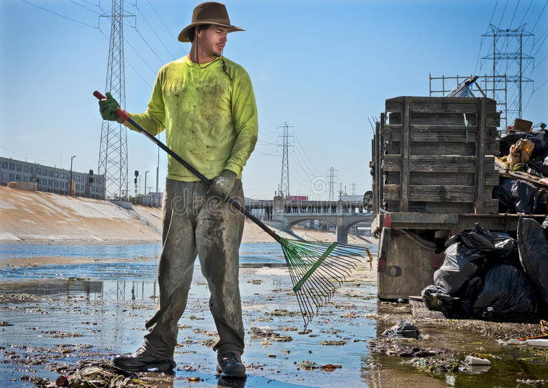 Cleaning The Los Angeles River, California. A man holds a rake as he works at his job cleaning the Los Angeles River, in downtown Los Angeles, California stock image