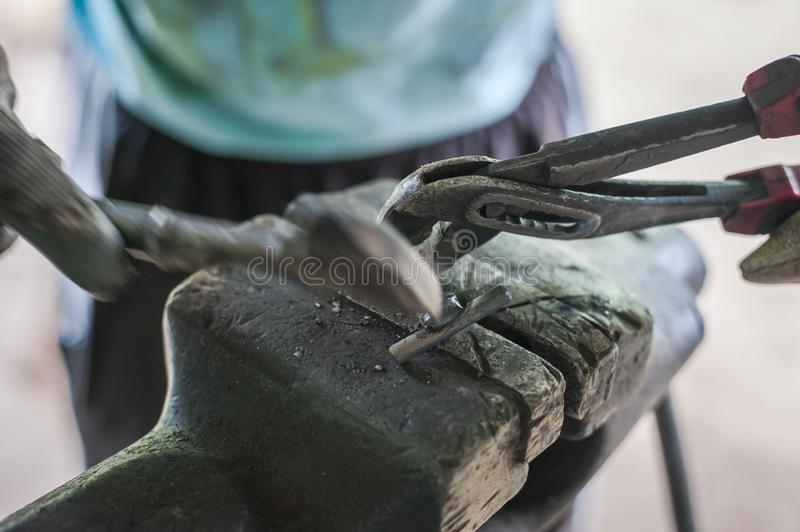 Cleaning metal with a hammer after welding. Steel, tool, work, industry, engineering, construction, industrial, safety, manufacturing, worker, labor royalty free stock photos