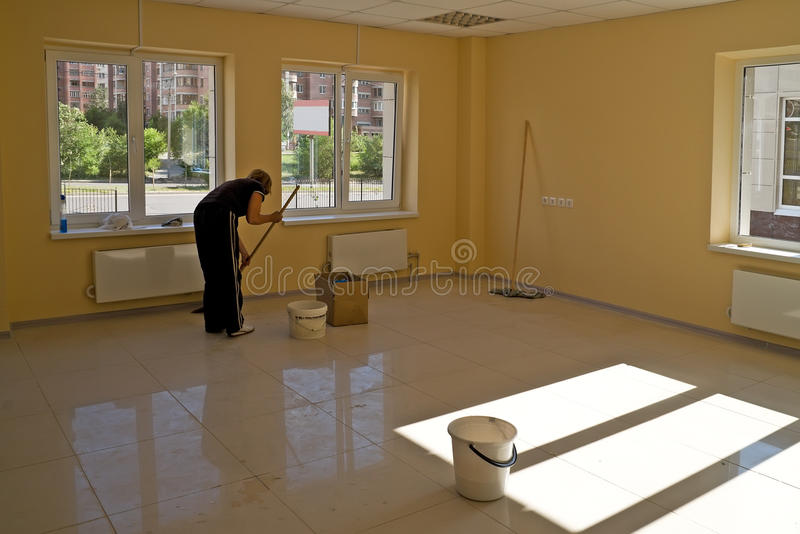 Cleaning in new office premise. Woman cleans new empty office premise with plastic windows with kind on city stock photo