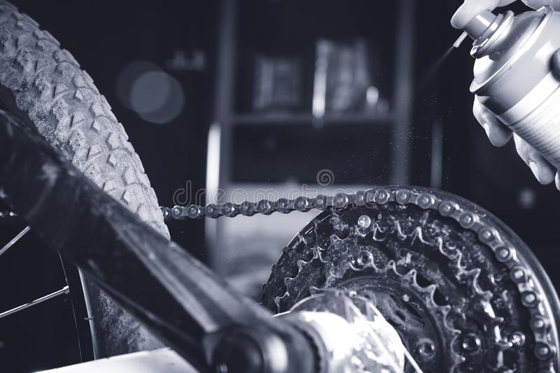 Cleaning and oiling a motorcycle chain and gear with oil Spray/dark light.  stock image