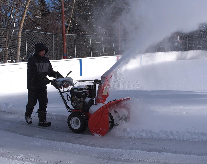 Cleaning Outdoor Hockey Rink. In winter after snowstorm in Edmonton Alberta February 2015 royalty free stock photo