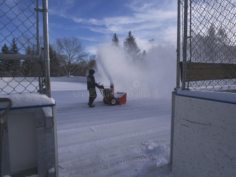 Cleaning Outdoor Hockey Rink. In winter after snowstorm in Edmonton Alberta February 2015 royalty free stock photos