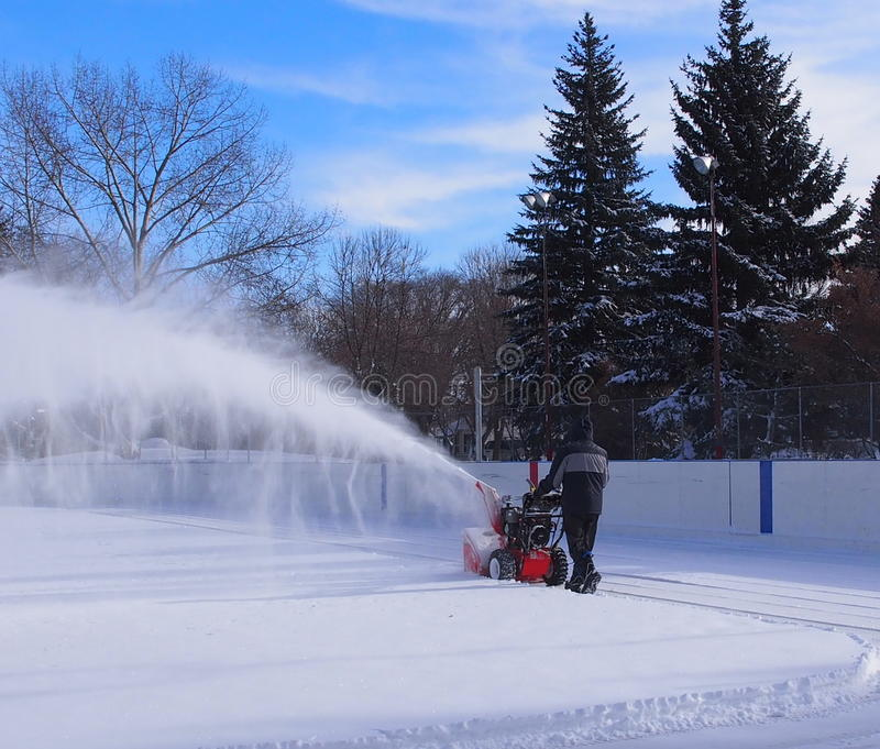 Cleaning Outdoor Hockey Rink. In winter after snowstorm in Edmonton Alberta February 2015 stock photography