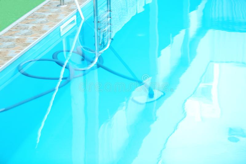 Cleaning outdoor pool with underwater vacuum,. Closeup stock images