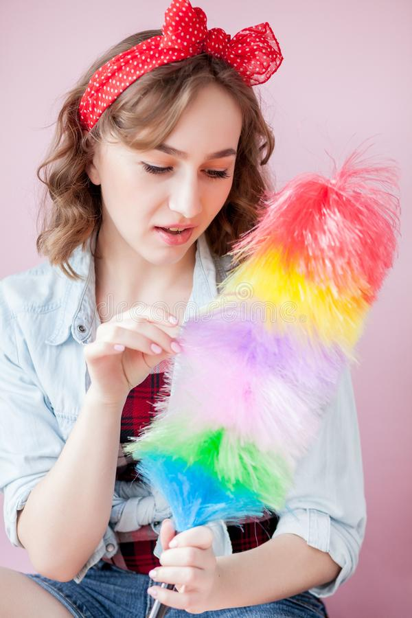Cleaning pin up woman. Smiling pinup girl holds colorful duster brush. Cleaning service. Pin-up girl cleaner with feather duster. Retro woman with cleaning stock photo