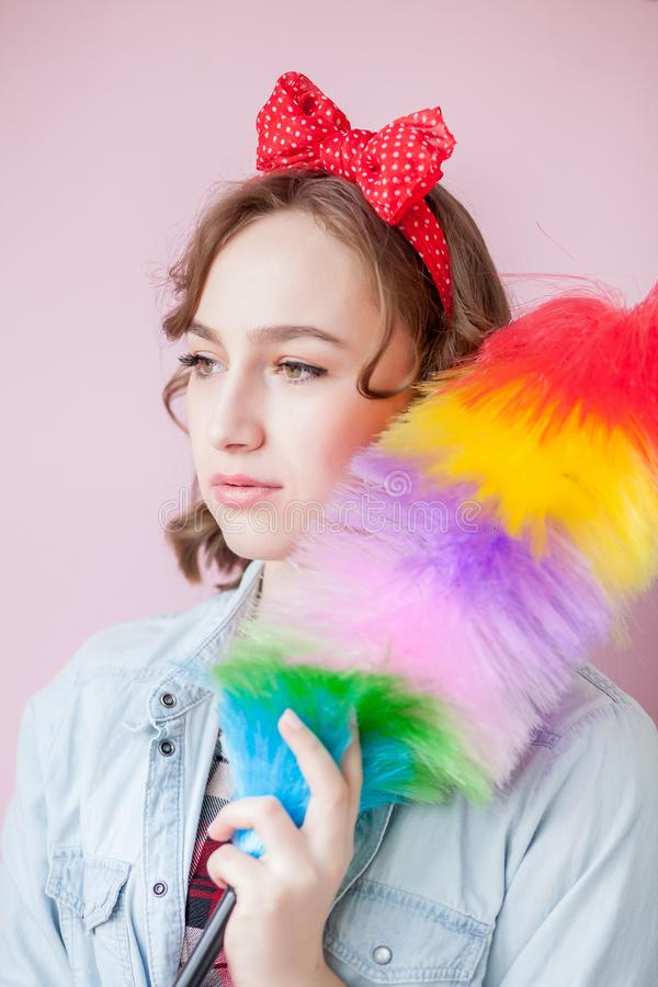 Cleaning pin up woman. Smiling pinup girl holds colorful duster brush. Cleaning service. Pin-up girl cleaner with feather duster. Retro woman with cleaning stock image