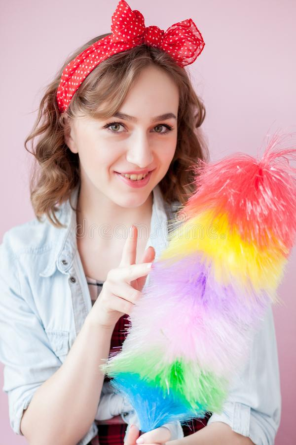 Cleaning pin up woman. Smiling pinup girl holds colorful duster brush. Cleaning service. Pin-up girl cleaner with feather duster. Retro woman with cleaning royalty free stock image
