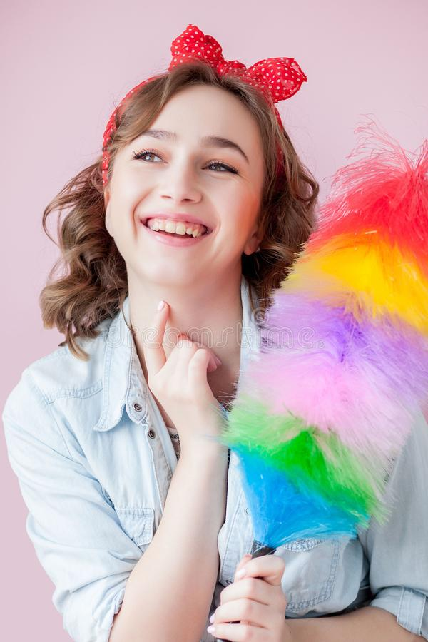 Cleaning pin up woman. Smiling pinup girl holds colorful duster brush. Cleaning service. Pin-up girl cleaner with feather duster. Retro woman with cleaning royalty free stock photography