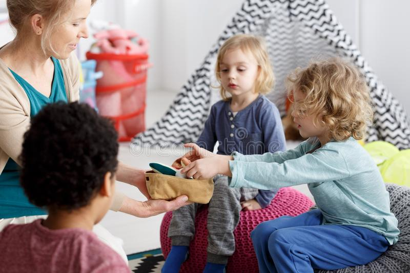 Cleaning after play. Little kids and their teacher cleaning toys after play stock photos