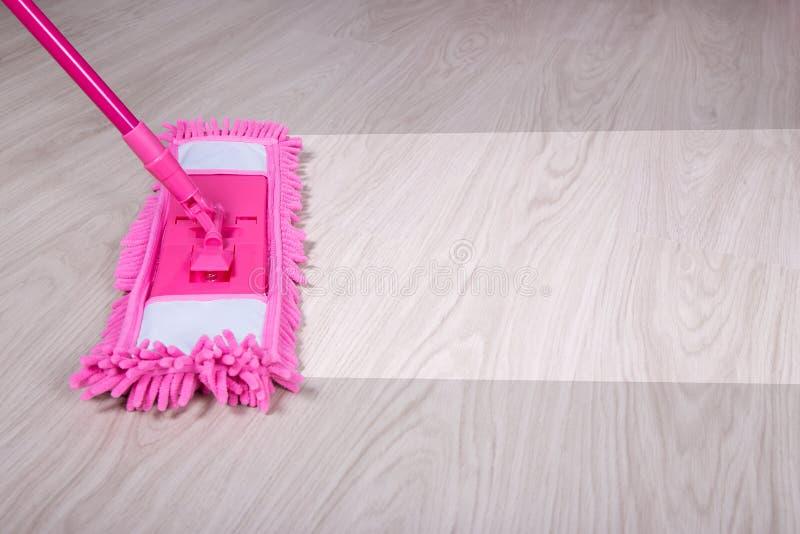 Cleaning pojęcie - zamyka up kwacz czyści drewnianej podłoga obrazy royalty free