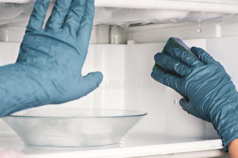 Young hostess with gloves washes a refrigerator. royalty free stock photos