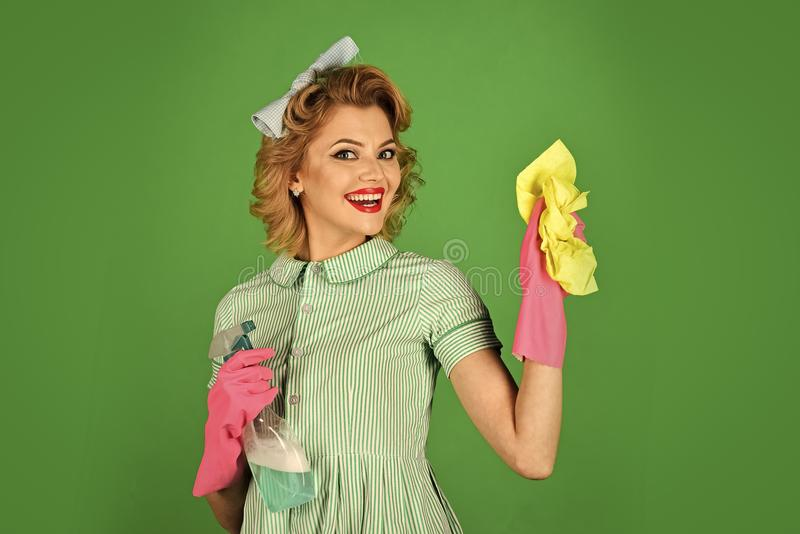 Cleaning, retro style, purity. Cleanup, cleaning services, wife, gender. Retro woman cleaner on green background. Housekeeper in uniform with clean spray royalty free stock images