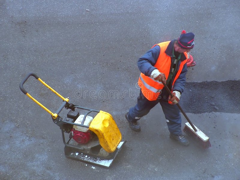 Cleaning the road. Road mender at work; hard work, power, blue-collar concept