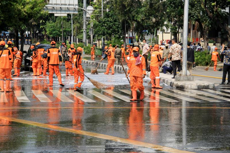 Cleaning Road in Jakarta. Jakarta, Indonesia - May 23, 2019: Officers cleared Jalan MH Thamrin after the Jakarta riots on May 22 royalty free stock photo