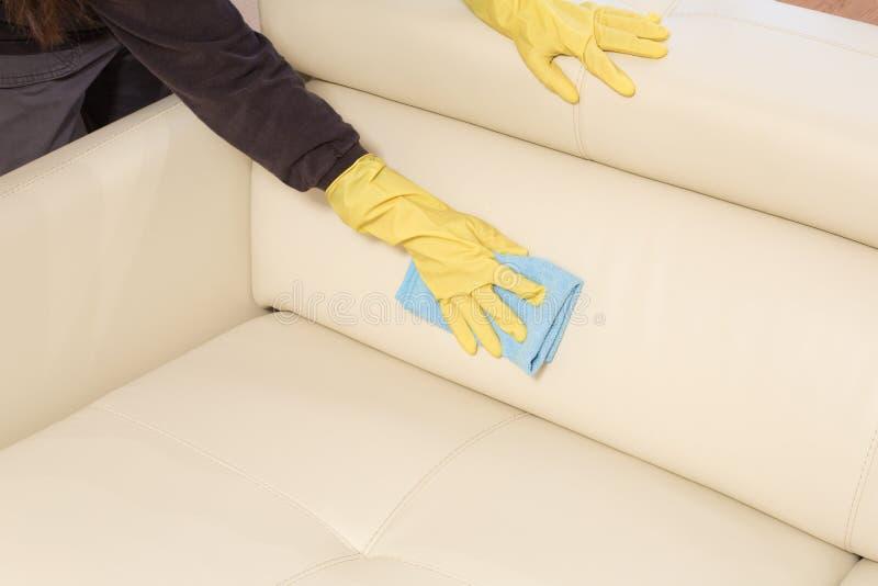 Cleaning rzemienna kanapa z łachmanem przy domem zdjęcia royalty free