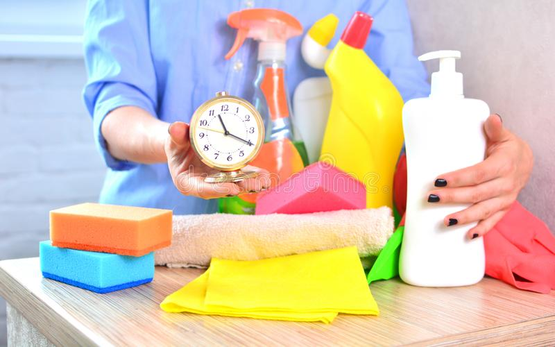 Cleaning service background with household chemicals and clock. Concept of cleanliness and freshness in the house with a saving time stock image