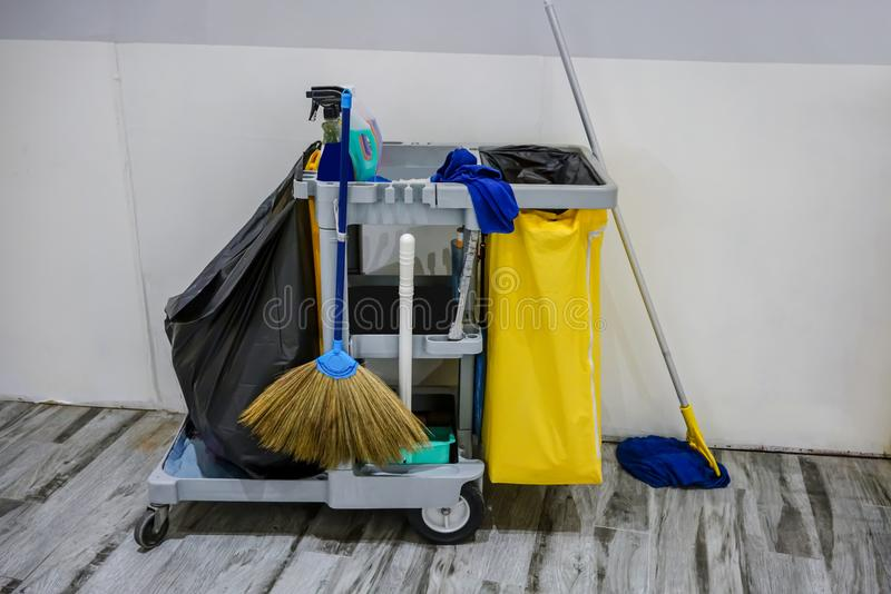 Cleaning service cart full of supplies and equipment along with. Yellow trash for professional cleaner against white wall royalty free stock photos