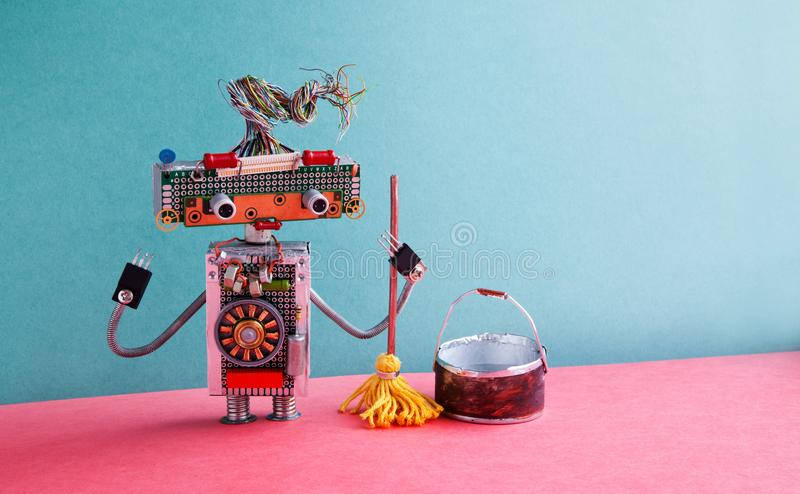 Cleaning service concept. Friendly robot washer mopping floor. Creative design cyborg toy with yellow mop, bucket of royalty free stock photography