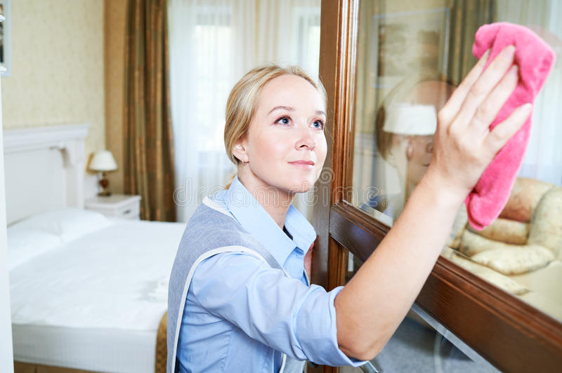 Cleaning service. hotel staff clean glass door from dust. Cleaning service. Female hotel staff worker clean glass door from dust and spot royalty free stock images