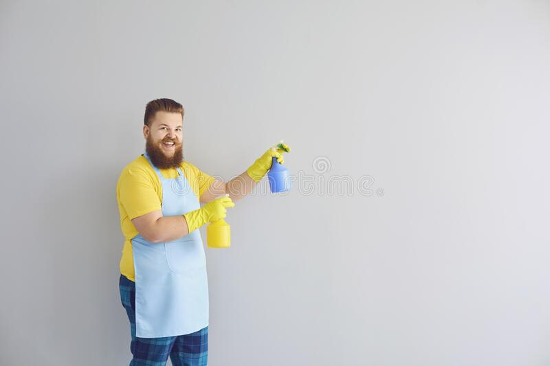 Cleaning service and housework concept. Happy funny guy with detergents on grey background, space for text royalty free stock photography