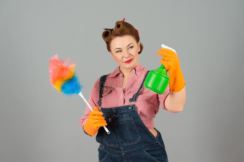 Cleaning female with duster and spray in denim in pin-up style. Housekeeper brunette girl posing stock images