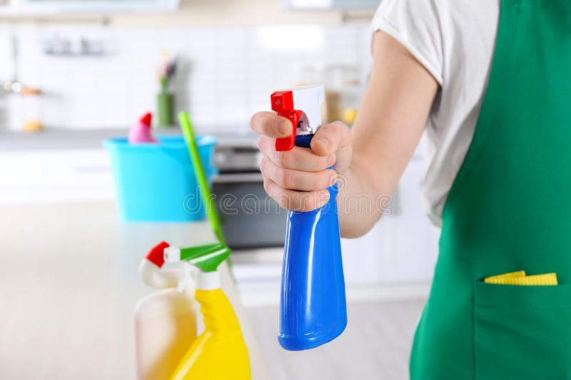Cleaning service worker holding bottle with cleanser,. Closeup stock photo