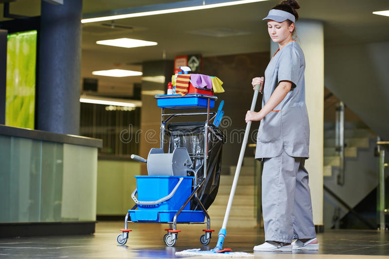 Cleaning services. Female cleaner with mop and uniform cleaning hall floor of public business building