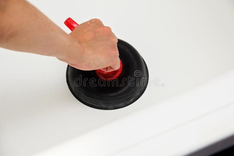 Cleaning the sewer in the bath. stock image