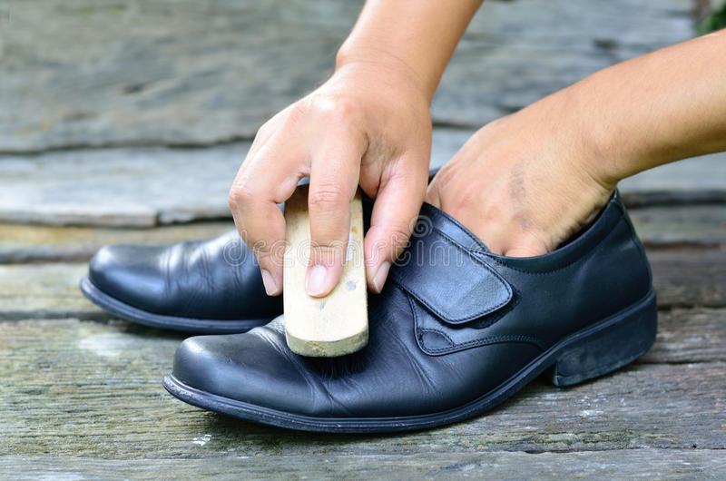 Cleaning shoes by hand. A hand cleaning a pair of black shoes royalty free stock image