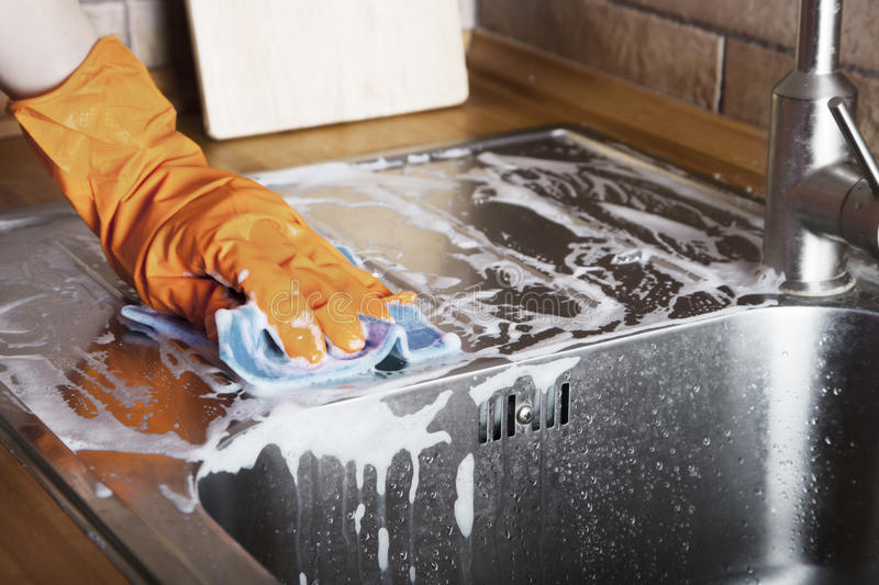 Cleaning sink. Rubber gloved hand cleaning sink with duster royalty free stock photography
