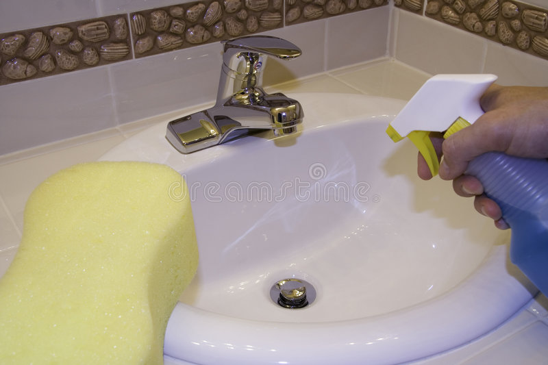 Cleaning the sink. With cleaner royalty free stock photography