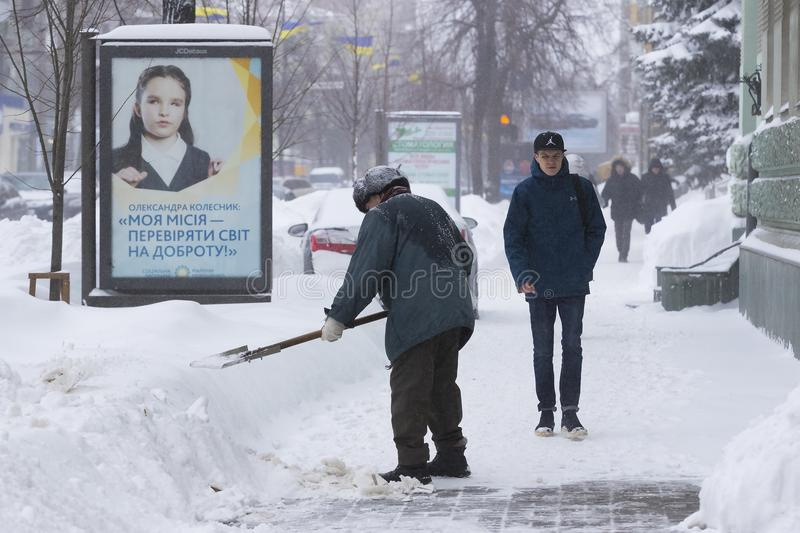 Cleaning of the streets of the city by residents and public utilities in the period of climatic cataclysm of large snowfalls. stock images
