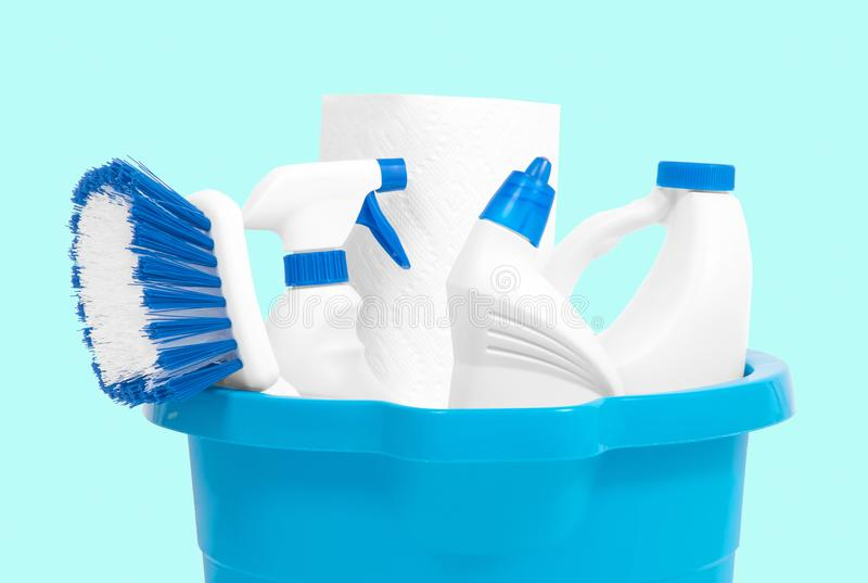 Cleaning supplies in blue bucket on pastel green background royalty free stock photo