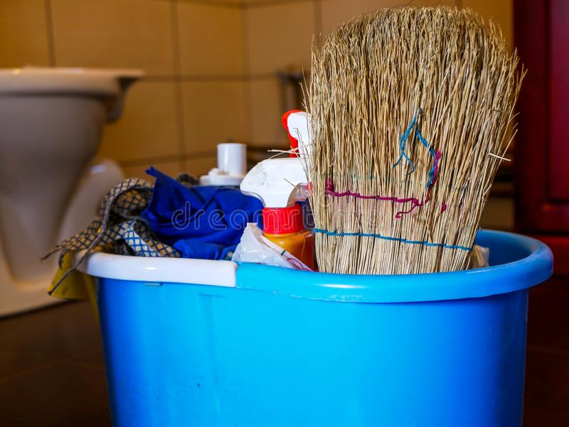 Cleaning supplies in blue plastic bucket close up shot at the entrance of a dirty bathroom royalty free stock photography