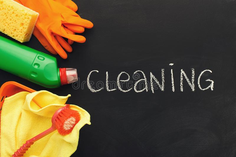 Cleaning supplies and products for home tidying up. House cleaning products and supplies on black chalk board background, top view. Spring cleaning and household royalty free stock images